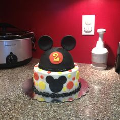 Mickey mouse birthday cake. Half ball pan covered in fondant for Mickey hat. Bottom covered in buttercream with fondant accents.