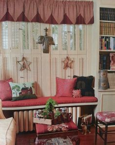Beautiful window seat with 2 sets of shutters for privacy topped with a red gingham valance. Via Country Sampler Magazine