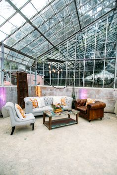 Lounge with Edison bulb lighting, recycled wood coffee table, vintage door, retro prints, and bright florals for a bohemian party in a rustic greenhouse on the Gaviota Coast.  Santa Barbara, California.    Event Production and Design by Tyler Speier Events and Photography by David Mendoza III.  Rentals by The Tent Merchant and lighting by Bella Vista Designs.