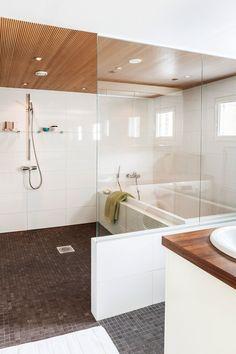 Avarassa kotikylpylässä vanhemmat voivat saunoa ja lapset lutrata kylpyammeessa. Kymmenen vuotta vanha kylpyhuone toimii edelleen hyvin. Lasiseinä rajaa kodinhoitotilan. Sormipaneelikatto jatkuu saunan puolelle. Suihku on Axorin.