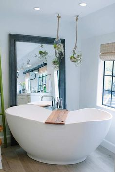A freestanding tub fitted with a polished nickel tub filler sits catty corner on wide plank wood floor tiles under terrarium hanging vases hung in front of a black metal beveled leaning floor mirror and a black window dressed in a bamboo roman shade.