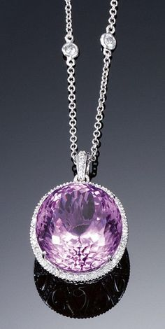 KUNZITE AND DIAMOND PENDANT NECKLACE. Centring on an oval kunzite, within a border of millegrain-set brilliant-cut diamonds, to a bezel of stylised scroll motifs set with lines of similarly-cut stones, on a fine chain spectacle-set with brilliant-cut diamonds, length approximately 420mm.