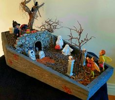 Miniature Fairy Garden - CHILDREN OF THE GRAVE. On Halloween, two boy fairies are ready to Trick-or-Treat. To his surprise, the younger boy fairy spots an old witch who lives above a stone cave. You can see the witch's cats, cauldron, broom, a bale of hay and pumpkins. Ghosts are seen scurrying down the hill. There are crows on the tombstones and dying trees and spiders at the graveyard. The boy fairies hesitantly plan to enter. 10/2016