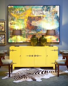 Bright yellow cabinet console with abstract art, modern lamps, zebra hide rug in a grey room - Via: Gary Riggs Home
