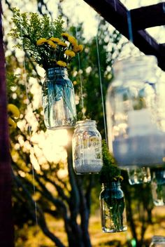 Mason jars with flowers and mason jars with candles hanging on a pergola for our wedding ceremony backdrop. We then took them off the hooks and moved them to the reception afterwards. Saves money!