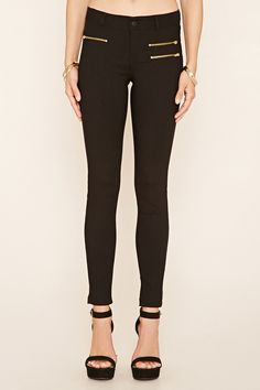 A pair of skinny jeans with three zippered front accents, two back patch pockets, and a zip fly.