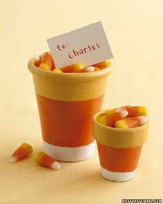 Candy Corn Pots - Decorate terra-cotta pots with yellow, orange, and white acrylic paint, and fill with candy corn for a festive Halloween treat.
