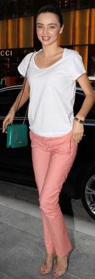 Easy way to wear the pale pink pants trend! Mirander Kerr pairs her Camilla & Marc ones with a white shirt, a green Bvlgari crossbody bag and nude Tabitha Simmons heels.