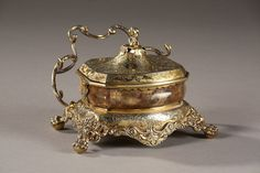 A silver-gilt and agathe inkstand resting on a flared base, very finely engraved and chiselled with foliated rinceau, scrolls and acanthus leaves, above four lions paws on balls. The...