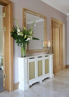 More formal entry/hallway decor ~ credenza with tall vase, fresh flowers and hurricane lamp or candle.