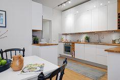 Renoverat luftigt kök med vita släta luckor