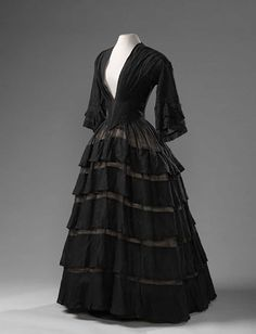 Black sheer wool muslin dress with five ruffles on the skirt and deep V neckline (to be filled in with a blouse or chemisette). Amsterdam Museum