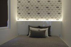 Stěnu ložnice zdobí vliesová tapeta s šedými a béžovými vějířky se stříbřitým přetiskem (346 Kč/role, návin 10,05 m x 53 cm, Schöner Wohnen), pro nepřímé osvětlení slouží vestavěný LED pásek za postelí