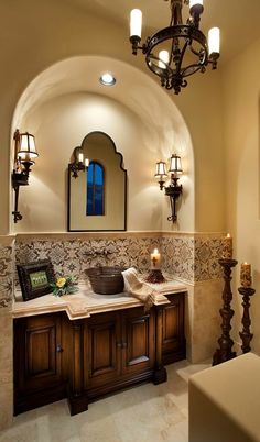 powder room- lovely tile accent, nice wall sconces and large floor candlesticks, beautiful stone countertop, simple, elegant lines of the mirror- only thing I would change is the sink.