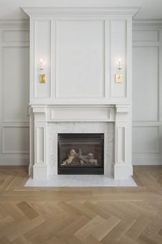 Traditional sitting room + herringbone flooring + white fireplace + wall paneling + art above fireplace + sconces on mantle + traditional fireplace design Fireplace Trim, Marble Fireplace Surround, Marble Fireplaces, Fireplace Wall, Living Room With Fireplace, Fireplace Design, White Fireplace Mantels, Fireplace Ideas, Classic Fireplace