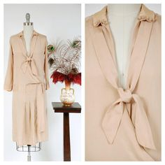 This vintage 1920s dress is completely disarming with its authentic charm, the true look of the flapper. Such a rare and wonderful find, piece is a classic summer look made of a lustrous ecru or khaki colored silk crepe de chine. The straight cut style closes offers long sleeves with accented cuffs. This quintessential late 20s drop waist dress wears open. The dress offers an iconic 20s silhouette, with straight cut bodice, darts at each shoulder, buttons on the neckline and pleated skirt…