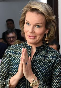 Queen Mathilde of Belgium, shows her respects by holding her hands in prayer position as a way of greeting. She accessories her look with gold swirled earrings, during their state visit in New Delhi, India