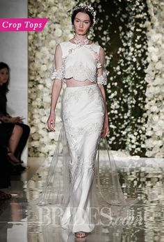 Crop Tops. We've seen a steady stream of crop tops for the past few runway rounds, but this season, there infiltrated the bridal world even more (hello Reem Acra). We spotted everything from a twinkling, belly-bearing sweater to layered separates with no skin showing at all.  Two-piece lace and silk sheath wedding dress with an elbow-length crop top, Reem Acra