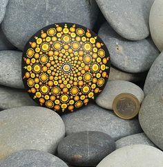 This hand-painted mandala rock is black with orange & yellow detailing. The rock has been coated twice with a clear varnish. Weight: 273g Length: 8.5cm Width: 8.5cm Depth: 2cm (All sizes are approximates measured at the widest point of each item as each item varies as it is natural rock.) If you have a special request for a mandala rock, please do not hesitate to get in touch! Maybe you have a specific colour design request, or you have a wedding and want a collection for wedding gifts, ...