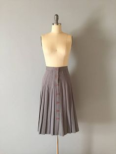 Vintage 70s midi skirt in dove gray color. Pleated wiggle accordion skirt with pinkish buttons to close down front. Fits like xsmall 26 waist 36 hips 28 length Tag: made in USA Material: cotton blend Excellent condition