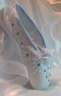 Elegant white and blue decorated pointe shoe. Organza roses, rose buds, lace, and Swarovski crystals are used to evoke the nightgown Clara wears