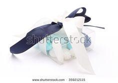 Blue and white sugared almonds in transparent plastic box