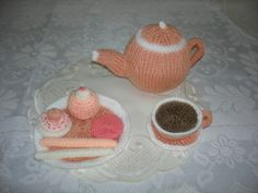 PEACH TEAPOT, CUP OF TEA, PLATE, CAKES AND BISCUITS