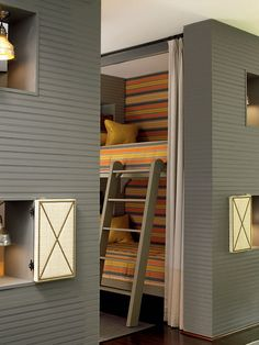 Bright orange stripes make each bunk feel like its own little nook. Small cutout cubbies serve as bedside tables, and upholstered doors close for more privacy.