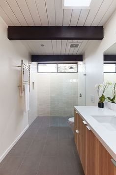In this modern ensuite bathroom, large grey tiles cover the floor, while light colored tiles and a glass surround keep the shower bright. #ModernBathroom #BathroomDesign