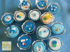 Baby shower cupcakes.  Includes embossed toppers, buttons, dummy, bottle, duck, rattle, bibs, abc, boy, safety pins, blocks.