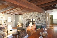 Exquisite stone surround to wood stove separating the great room from the kitchen; huge timber beams, plenty of sunlight... a great great space.