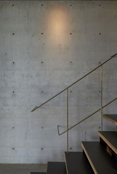 Throughout the 4,607-square-foot residence, the materials used in the built environment speak to the natural environment. Here, raw brass railings and inserts in the concrete wall plugs give off a star-like glimmer in the gallery, which originally showcased the homeowner's art collection.