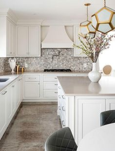 Beautiful off-white kitchen boasts an off-white island accented with satin nickel pulls and a taupe quartz countertop lit by two Robert Abbey Pythagoras Pendants.