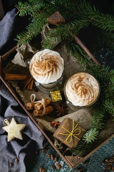 Pumpkin spicy latte with whipped cream and cinnamon in two glasses standing in wooden board with textile and Christmas decoration and fir tree other dark background. Christmas Coffee, Christmas Mood, Christmas Treats, All Things Christmas, Christmas And New Year, Christmas Decorations, Christmas Food Photography, Christmas Aesthetic, Christmas Pictures