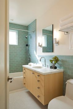 Sea glass shower tile, light floors, light cabinets