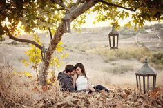engagement picnic date | under a tree with lanterns hanging from low tree branches