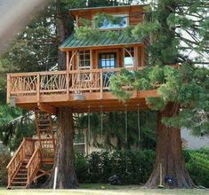 Great treehouse with beautiful railing with swing set beneath it.