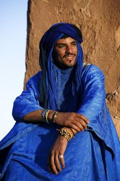 Tuareg man, dressed in traditional clothing, with Ait Benhaddou Kasbah in the background. Near the town of Ouarzazate. Morocco.
