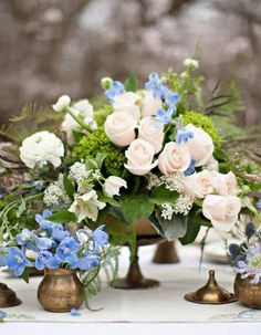 Almond-Orchard photo shoot. Pedestal or compote arrangement with white roses, blue delphinium, tweedia, ferns. In mixed types of brass containers