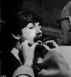 """Paul McCartney (getting his disguise put on at Marylebone Station during the filming of A Hard Day's Night.  Scanned from """"The Beatles Film"""" souvenir magazine 1964)"""