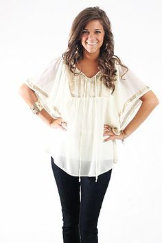 """Golden Child Blouse $38.00 This top is absolutely beautiful! We love the ivory with the golden accents! This would be the perfect top for the Christmas and New Year's season! Grab yours before they go!   Fits true to size. Miranda is wearing a small.   From shoulder to hem:  Small- 26""""  Medium- 27""""  Large- 28"""""""