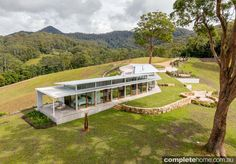 With sweeping grand views of its hilly verdant surrounds and an environmentally conscious design, this home near Coffs Harbour is an ideal country retreat
