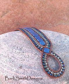 «La princesse diamant en daim Bleu»  La «princesse» est une version de «La Reine des diamants». Le point focal de la princesse est ses deux 2 «diamants» tchèque Suède bleu tuile de perles de verre. Elles sont cousues dans un cordon tressé en détresse-finition indien en cuir marron clair. Autour de la rangée centrale de daim Bleu tuile perles, sont 2 deux doubles rangées de perles de rocaille en Nickel et Cosmos métallique. Fermeture à l'avant est une argenté 5/8 bouton de Bali avec…