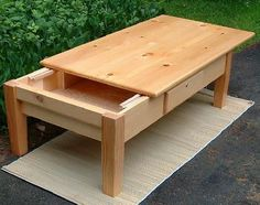 Pine top coffee table with sliding top reveals a hidden storage compartment. The company that makes this, False Bottom Productions, has a number of unique hand built items on their website.