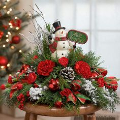 Frosty Tidings #37614 by Viviano Flower Shop | holiday arrangement with evergreens, carnations, and a snowman, our favorite jolly happy soul to have around this Christmas!