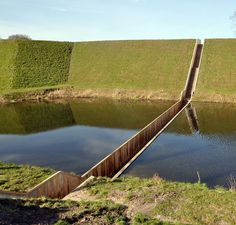 """Early 17th century Fort de Roovere is surrounded by a moat and was originally built without a bridge. Yet, as part of a recent restoration program, it required the addition of an access bridge. Out of respect for the fort's original island status, Netherlands-based RO Architecten  constructed the Moses Bridge Stairs, a discreet """"sunken"""" bridge that sits flush with the line of the soil and the water. The result is an almost invisible bridge that partially immerses pedestrians into the moat."""