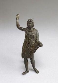 """Говорят, что из Александрии, город в Египте, основанный Александром в 331 г. до н.э., эта маленькая бронзовая статуэтка изображает юную Александр с длинными, полные волос. Его волосы, с характерным """"anastole"""", и форма его лица привели ученых к постулировать, что этот портрет происходит от оригинала Lysippan, созданный при жизни Александра. Александр выступает в """"контрапост"""" с весом на правой ноге. Его правая рука поднята, и он, вероятно, держал копье или копье в этой руке. Эта статуэтка…"""