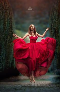 Beautiful woman floating in a red dress