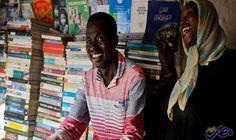 جمعة علي يسعى إلى نشر الثقافة في…: ينظر جمعة علي، بائع الكتب، باعتزاز إلى أكوام الكتب في الجزء العلوي من مكتبته المؤقتة، والتي تضم مجموعة…