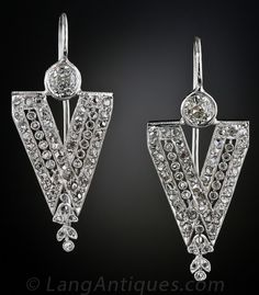 Edwardian Diamond Earrings, These stunning and dramatic Edwardian platinum and diamond earrings, dating back to the early-twentieth century, are composed of sleek diamond 'V's twinkling with numerous tiny rose-cut diamonds. The diamond 'V's are each crowned with an old mine-cut diamond set in milgrained bezels (and were most likely added later). These vintage sparklers measure 1 and 1/8 inches long.